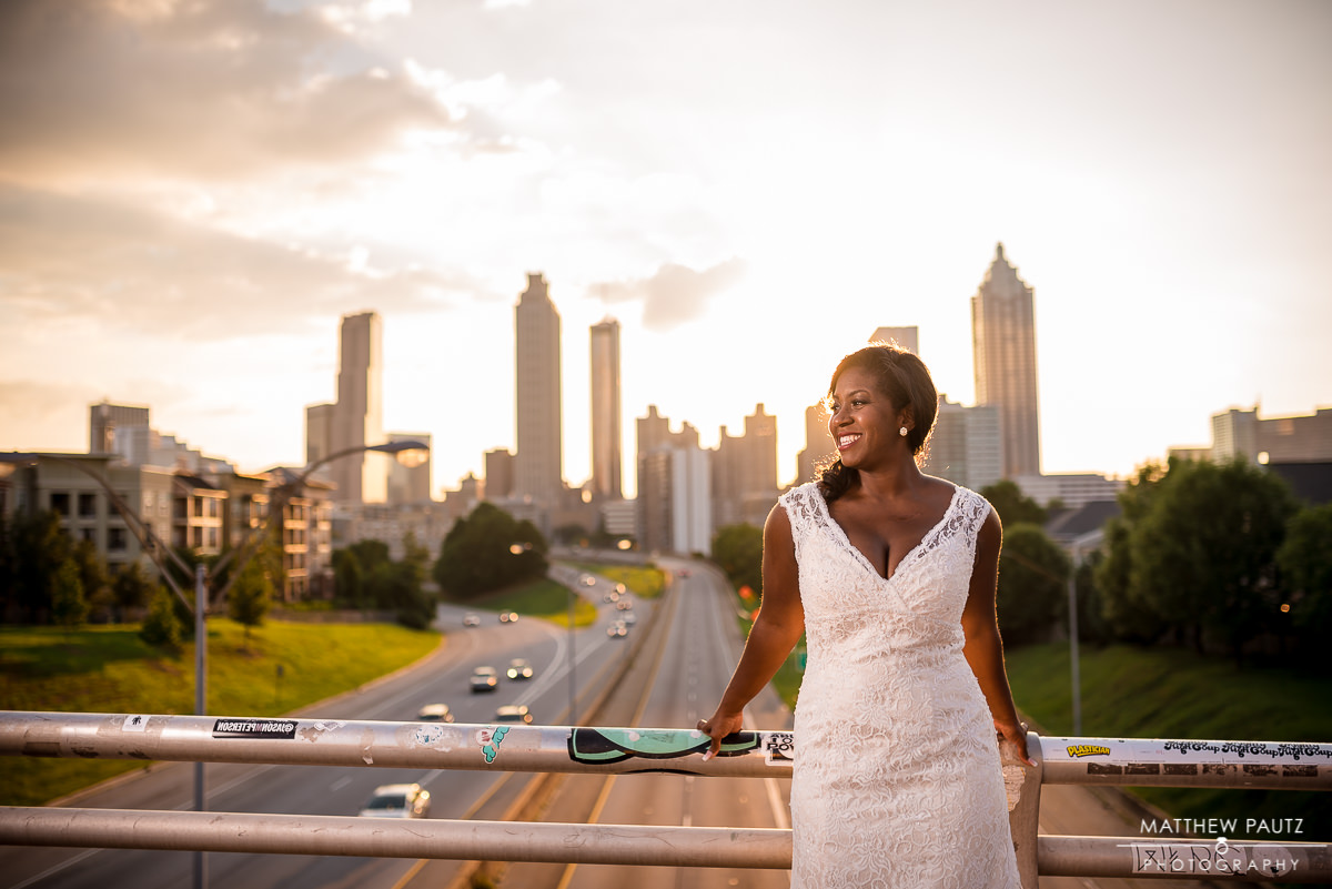 Smiling bride in wedding dress looking out over Atlanta skyline at sunset