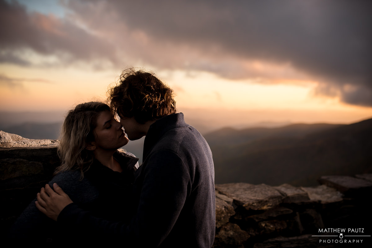 couple kissing on a mountaintop during a dramatic sunset