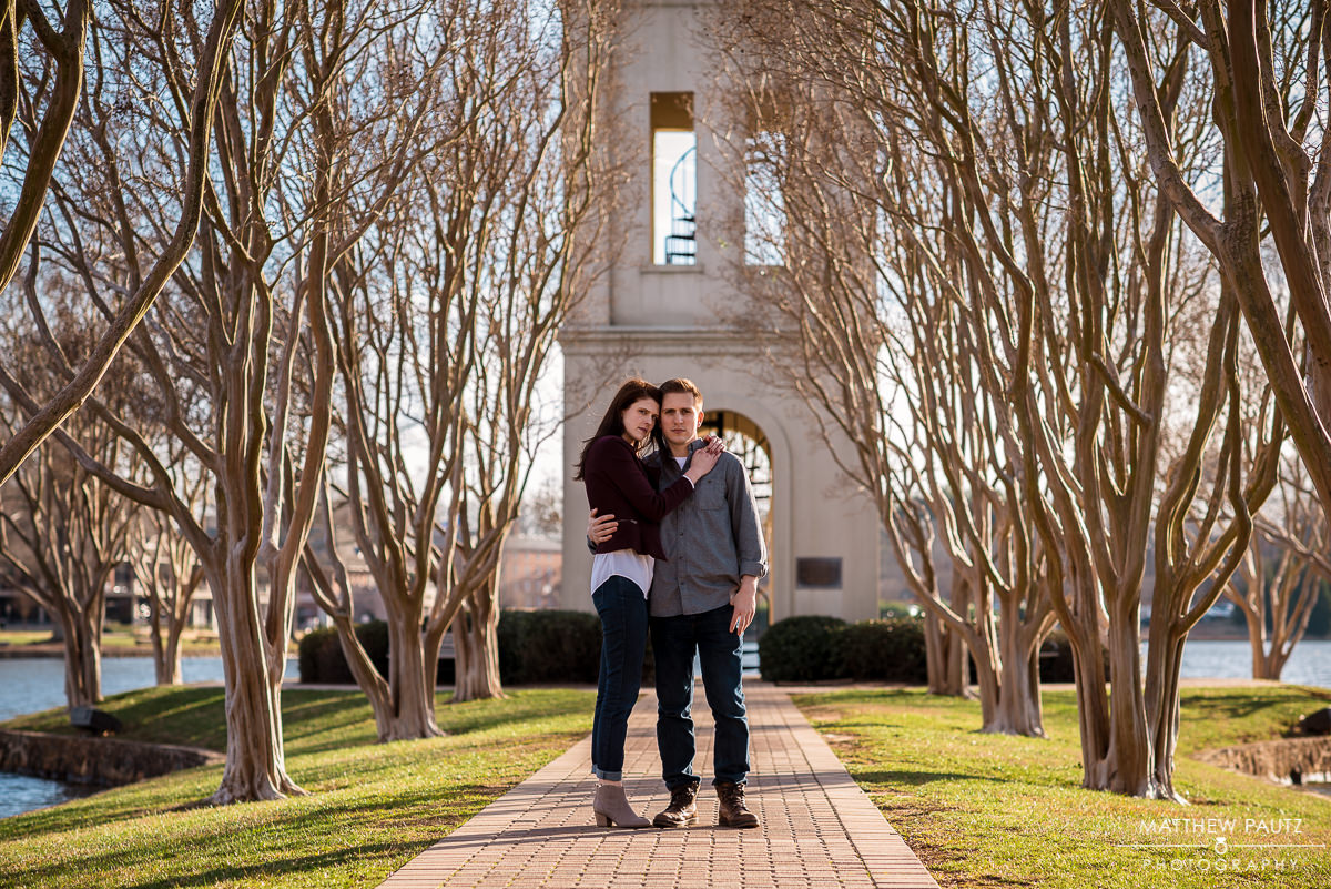 Engaged couple hugging in front of Furman university's bell tower