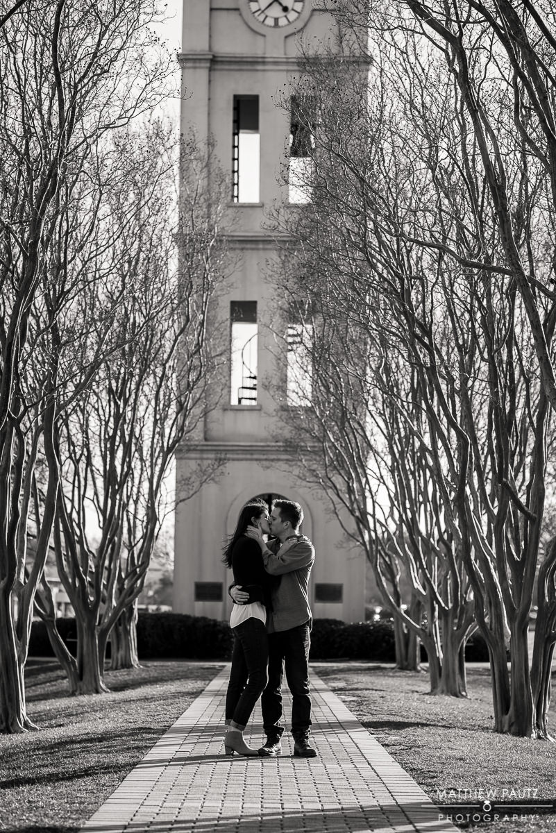 Engaged couple kissing in front of Furman university's bell tower