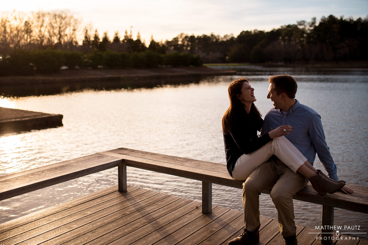 engaged couple laughing and holding hands at the lake