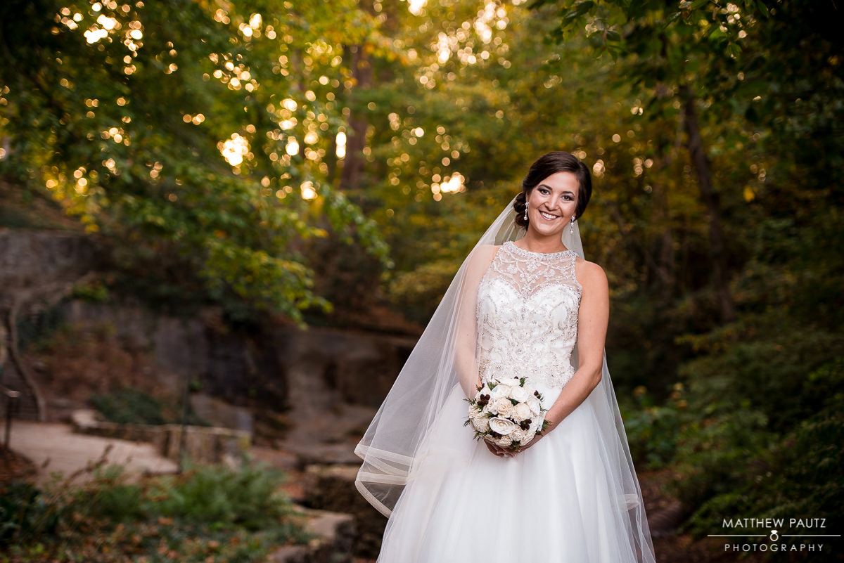 bride holding flowers in park during Fall