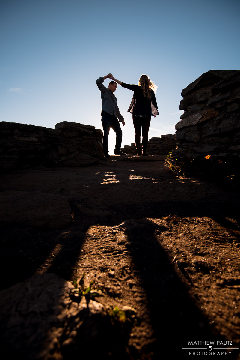 couple dancing on mountaintop at sunset