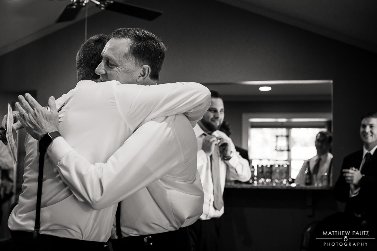 Groom hugging father before wedding