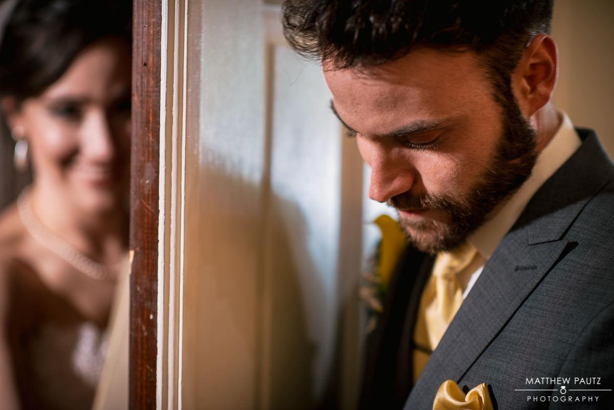 Bride and groom holding hands across doorway