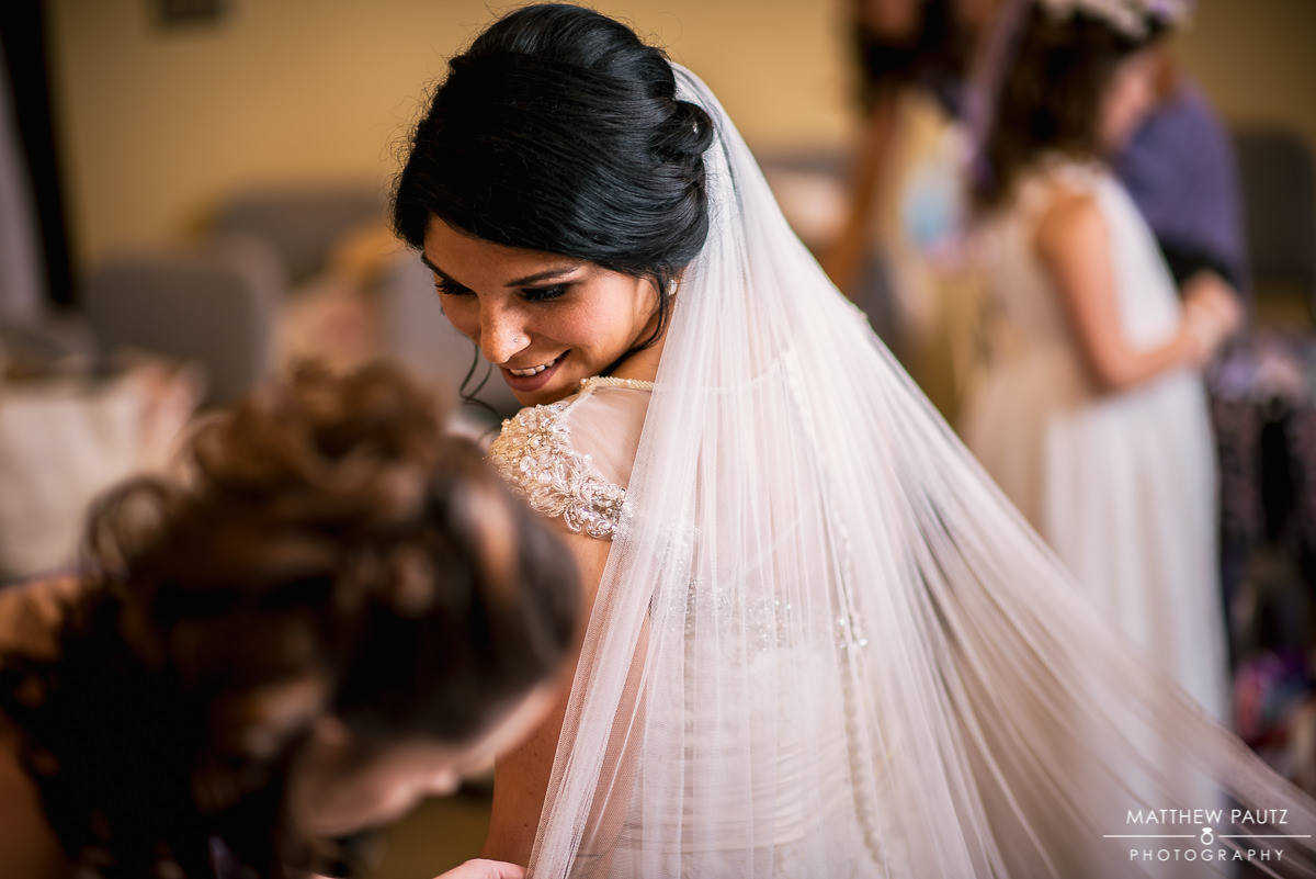 bride looking at bridesmaid after having veil put in