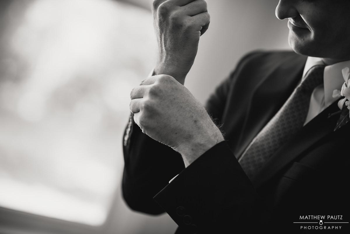 groom adjusting his cuffs before wedding ceremony